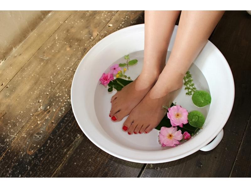 bain de pieds au sel dans une bassine blanche avec des fleurs roses